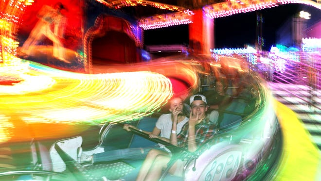 """North Florida Fair visitors ride the """"Music Express"""" during the fair's opening night Thursday. On Saturday, a 14-year-old girl was flung from the ride, her mother claiming the girl's nose was broken as a result, blaming what she thinks are inadequate lap restraints."""