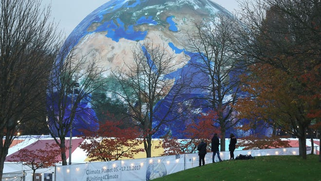 "People walk past the ""Climate Planet"" exhibition at the United Nations Climate Change Conference."