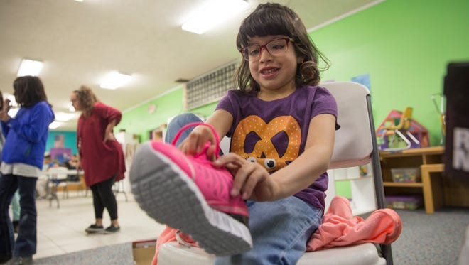 Trinity Vinson tries on her new shoes Friday during a shoes distribution program hosted by the Rio del Sol Kiwanis cflub at the Hilltop location for the Boys & Girls Clubs of Farmington.