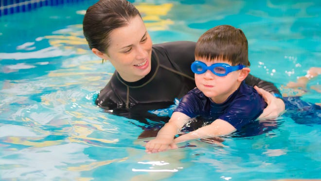 An Njswim instructor works one-on-one with a student to teach water safety and swimming fundamentals