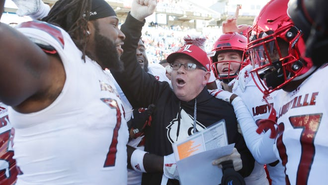 Louisville coach Bobby Petrino celebrated with his team after defeating Kentucky 44-17. Nov. 24, 2017.