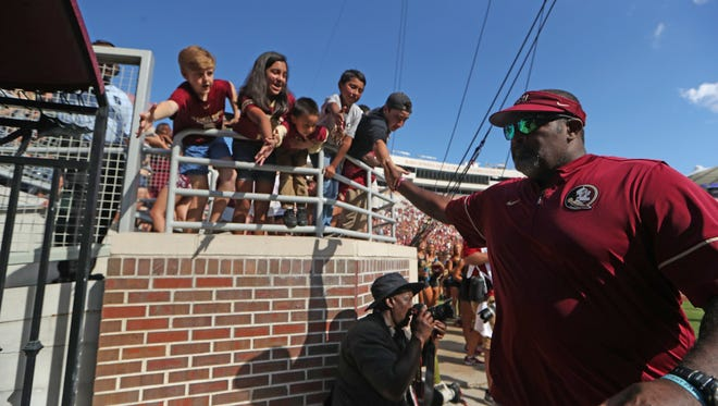 FSU Interim Head Coach Odell Haggins high-fives fans as he runs off the field in their first post-Jimbo Fisher era game against Louisiana Monroe at Doak Campbell Stadium on Saturday, Dec. 1, 2017.