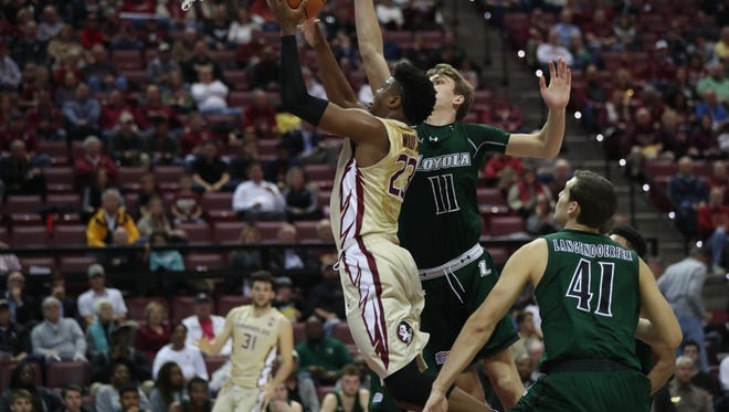 FSU's M.J. Walker lays the ball up against Loyola of Maryland's River Reed during their game at the Tucker Civic Center on Wednesday, Dec. 6, 2017.