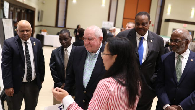 U.S. Secretary of Agriculture Sonny Perdue, center, joined by Congressman Al Lawson and FAMU President Larry Robinson speak with students about their agricultural research projects at FAMU on Friday, Dec. 8, 2017.