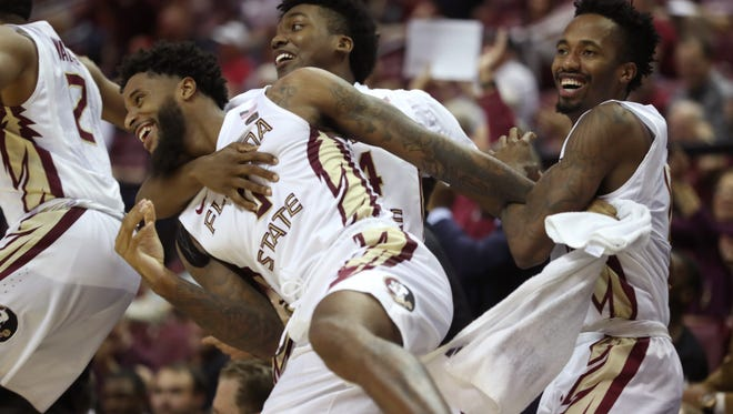 FSU's Phil Cofer, from left, Terance Mann and Braian Angola celebrtae the Seminoles 98-45 win over Southern Miss at the Tucker Civic Center on Thursday, Dec. 21, 2017.