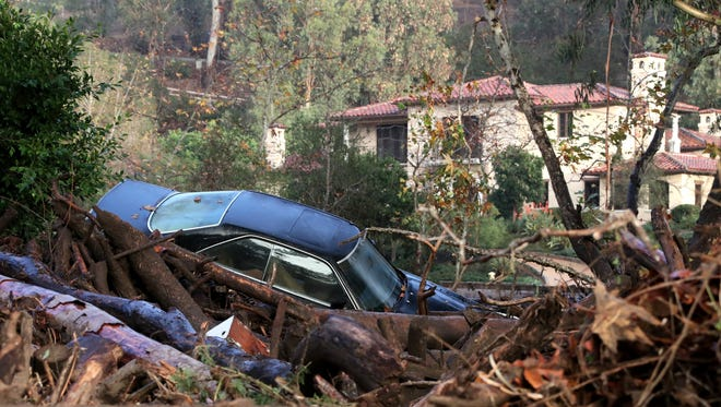 A car is buried in debris after a mudslide during heavy rains in Montecito, California, on January 9, 2018.