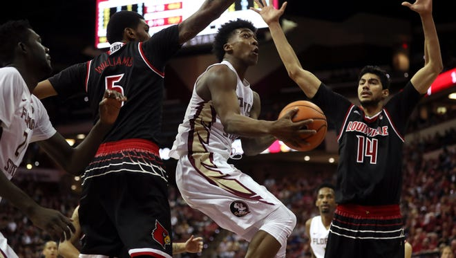 FSU's Terance Mann squeezes between the defense of Louisville's MalikWilliams, left, and AnasMahmoud for a layup during their game at the Tucker Civic Center Wednesday, Jan. 10, 2018.