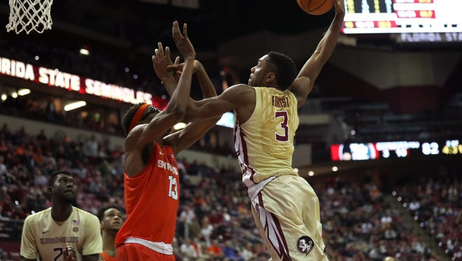 FSU's Trent Forrest goes up for a dunk against Syracuse's PaschalChukwu during their game at the Tucker Civic Center on Saturday, Jan. 13, 2018.