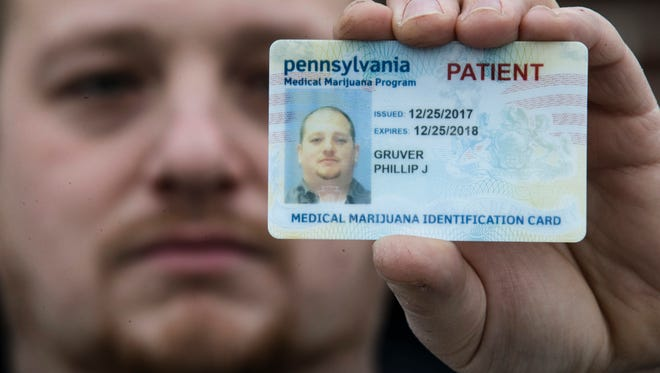 In this Wednesday, Jan. 10, 2018 photo Phil Gruver poses for a photograph with his Pennsylvania with his medical marijuana card in Emmaus, Pa. As gun-loving Pennsylvania becomes the latest state to operate a medical marijuana program, with the first dispensary on track to begin sales next month, authorities are warning patients that federal law bars marijuana users from having guns or ammunition. Gruver is weighing what to do with his .22-caliber rifle and a handgun he keeps for home defense.
