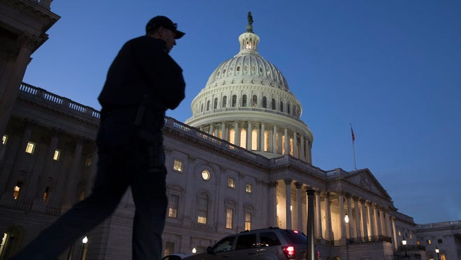 A Capitol police officer walks in front of the Capitol building at dusk after the House passed a short-term measure to fund the federal government.