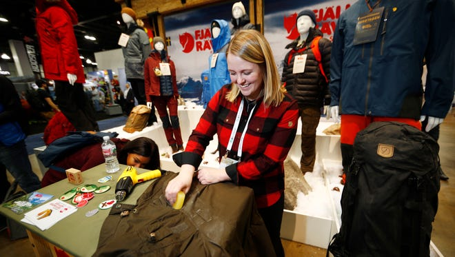 Aundrea Dawkins of Louisville, Colo., puts a protective wax on a Fjallraven coat in the Swedish company's booth at the Outdoor Retailer and Snow Show in the Colorado Convention Center Friday, Jan. 26, 2018, in Denver. Sales of outdoor equipment are slipping as millennials drive changes in U.S. consumer habits by favoring clothes and sporting goods that are less specialized and more versatile, analysts say.  (AP Photo/David Zalubowski)