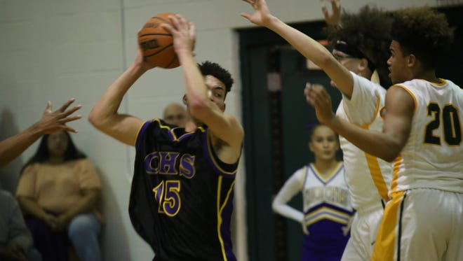 Clarksville High's Devyn Bender keeps the ball away from Northwest defenders during their first half of their district game Friday night at Northwest High.