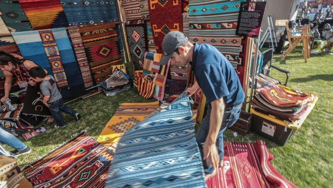 Artist Antonio Mendoza rolls one of his rugs at the Southwest Arts Festival at the Empire Polo Club in Indio on Saturday, January 27, 2018.