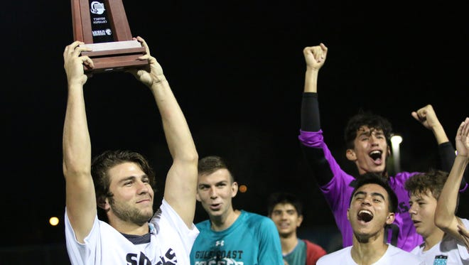 Cameron Heise hoists the Class 4A-District 12 championship trophy after the Gulf Coast boys soccer team defeated Palmetto Ridge, 1-0, on Friday.