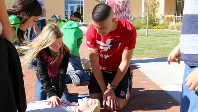Medical student Alex Lam shows local fourth-grade students the basics of CPR.