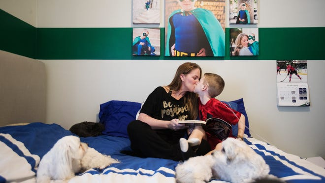 Brandi Lawrey kisses her son, Gavin after he did a good job of reading to her at before nap time. Gavin is battling mitochondrial disease and has been chosen as the Most Valuable Patient for the Boston Red Sox Children's Hospital Celebrity Classic.
