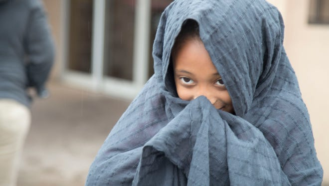 Amira Phason shields her face from the rain in downtown Phoenix on Feb. 14, 2018.