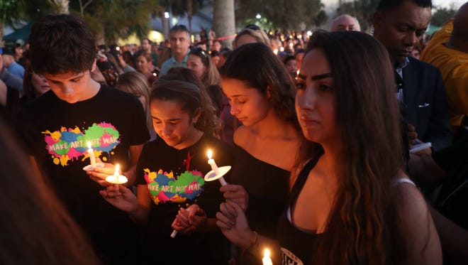 Mourners attend a Feb. 14 candlelight vigil for those slain and injured in a Valentine's Day mass shooting at Marjory Stoneman Douglas High School in Parkland. Thousands were in attendance for the vigil, at the  Pine Trails Park amphitheater in Parkland.