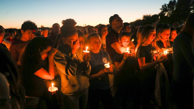 Mourners including students from Marjory Stoneman Douglas High School in Parkland, Florida attend a candlelight vigil at the Parkland Amphitheatre on Thursday 2/15/2018.