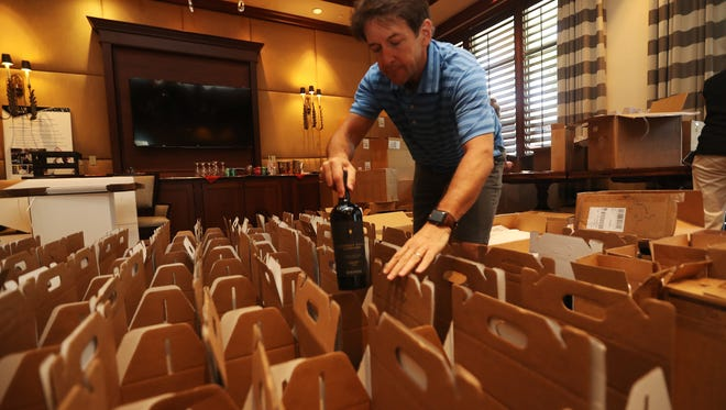 David Collins, a trustee of the SWFL Childrens Charities prepares for the Southwest Florida Wine & Food Fest at Quail est Golf &ountry Club in Naples on Thursday.