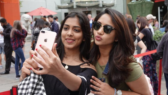 Two tourists from India take a selfie outside the TCL