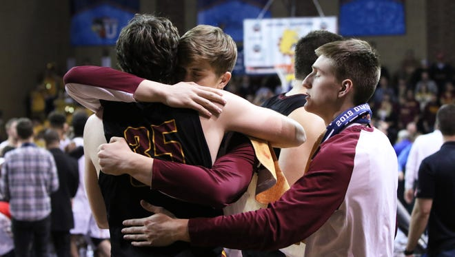 Logan Doyle of Northern State is consoled by his teammates following their loss to Ferris State in the NCAA DII National Championship game at the Pentagon.
