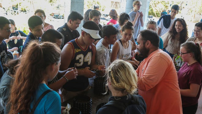 Kawika Davis from the University of Guam Plant Extinction Prevention Program, is making a difference by showing students from Guam High School how to plant Ifit seeds.