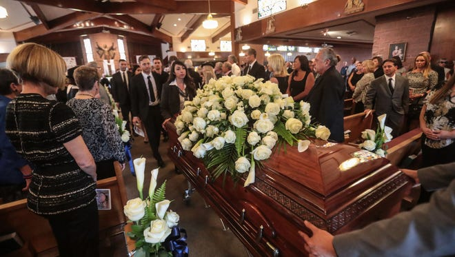 Jim Houston's casket is followed by his family at the end of the funeral service at Sacred Heart Catholic Church in Palm Desert on Thursday, April 5, 2018.