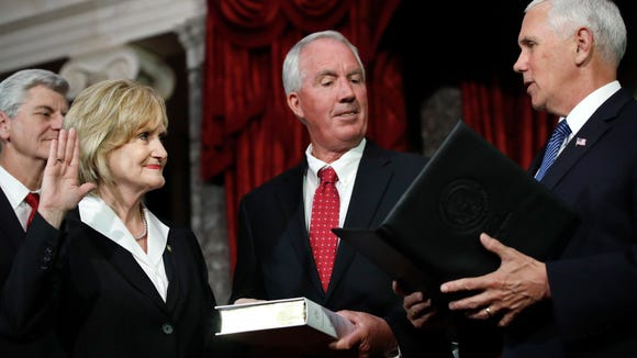 Mississippi Republican Cindy Hyde-Smith, left, is welcomed as the newest member of the U.S. Senate by Vice President Mike Pence, right, as she is joined by her husband, Michael Smith, center, and Mississippi Gov. Phil Bryant, far left, during a ceremonial swearing-in at the Old Senate Chamber, Monday, April 9, 2018, in the Capitol in Washington. She was appointed by Mississippi Gov. Bryant to succeed Sen. Thad Cochran, R-Miss., who resigned in April for health reasons. (AP Photo/Jacquelyn Martin) ORG XMIT: DCJM101