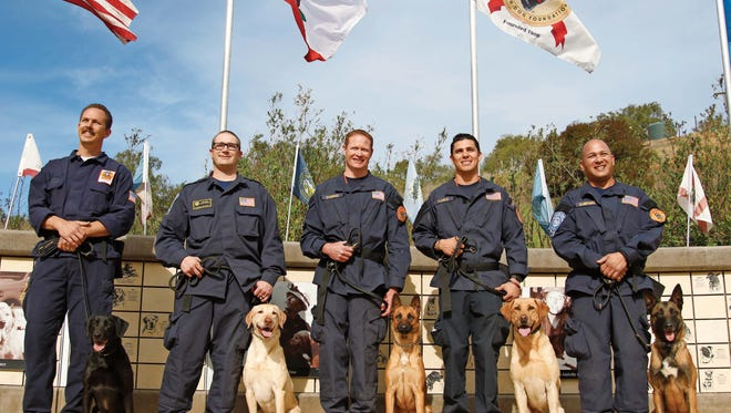 Firefighters from the Orange County, Calif., and Los Angeles County Fire Departments with their dogs at a 2016 search team graduation  ceremony.