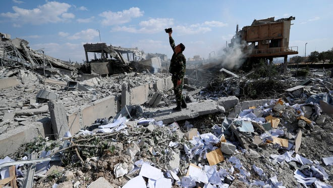 A Syrian soldier films the damage of the Syrian Scientific Research Center which was attacked by U.S., British and French military strikes.