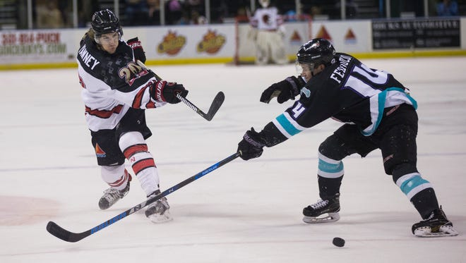 Conor Yawney shoots the puck past a Shreveport Mudbugs defender on Thursday at the American Bank Center.