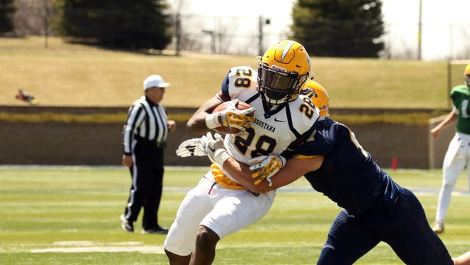Augustana RB, Rudolh Sinflorant attempts to escape the tackle by Kyle Theis during Saturday's spring game in Sioux Falls.
