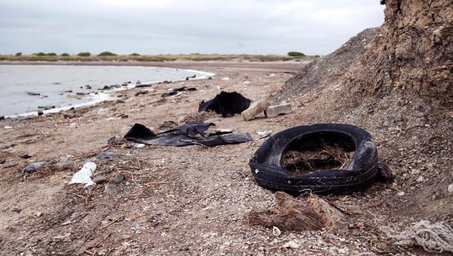 Trash, including this tire, litters the beach near Oso Bay just off Yorktown Boulevard on Tuesday, May 1, 2018.