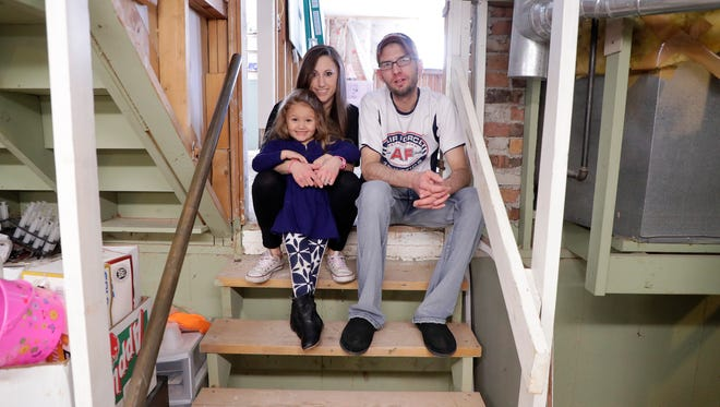 Matt, Brooke and Brinley Sorenson sit on the basement steps of their house at 3152 St. Gregory Drive in Green Bay. The home was flooded with 55 inches of water in February.