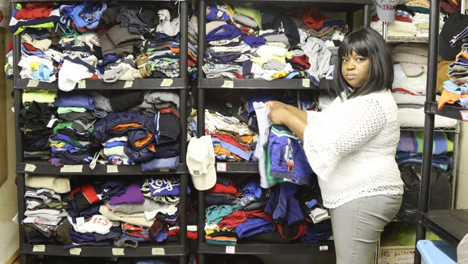 Sandra Fils of Catholic Charities for the Archdiocese of Newark with racks of children clothes that were contributed to be given to refugee children.