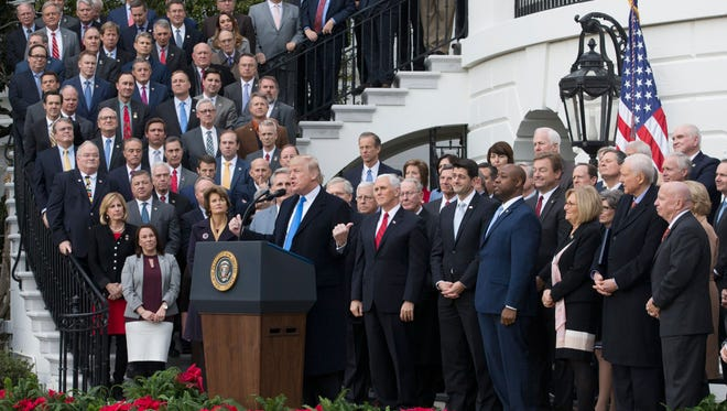 President Trump and GOP lawmakers celebrated passage of tax reform in December at the White House. Minnesota legislators and the governor are debating how to amend the state's tax code to best match federal changes.