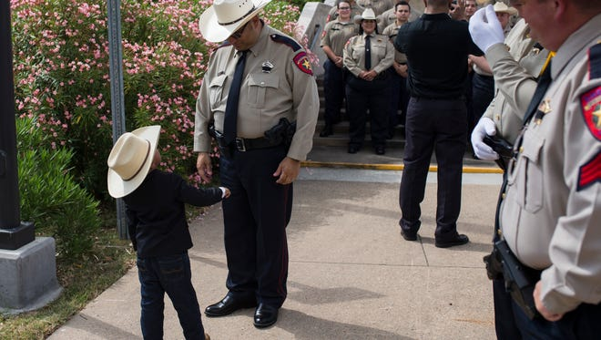 Logan Steel Garza, 4, greets his father, Nueces County Sheriff's Deputy Corando Garza, following a ceremony honoring fallen officers on Tuesday, May 15, 2018, outside the Nueces County Courthouse.