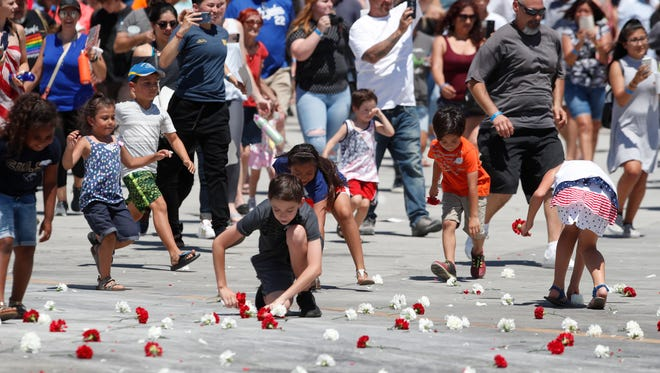 Children, men and women pick up carnations after they were dropped from a B-25 Bomber during Memorial Day celebrations held at the Palm Springs Air Museum.