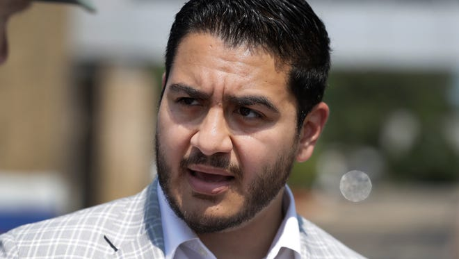 FILE - In this Aug. 8, 2017, file photo, Dr. Abdul El-Sayed talks with citizens in Detroit. Second-term Gov. Rick Snyder's impending departure under term limits has led four Republicans and three Democrats into a battle to follow him. The Democratic side features former Senate Minority Leader Gretchen Whitmer and two candidates who have never held elective office: businessman Shri Thanedar and ex-Detroit health director Abdul El-Sayed. (AP Photo/Carlos Osorio, File)