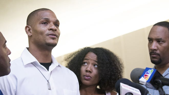 Robert Johnson, a 33-year-old man (center) who was beaten by Mesa police officers in May, attorney Benjamin Taylor (left), and Johnson's fiancée speak at New Beginnings Christian Church in Mesa on June 7, 2018. This is the first time Johnson has spoken publicly since the incident.