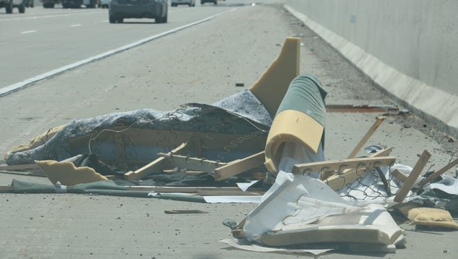 The discarded remains of a piece of furniture have sat along southbound I-465 for weeks.