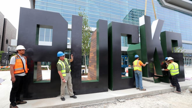 "As Milwaukee Bucks guard Malcolm Brogdon (left) looks on, workers with the De Pere-based Jones Sign Company, including account executive Patrick Basche, who recorded the event on his mobile phone, lower the ""K"" into place. Unveiled Thursday, the large BUCKS ""monument"" sign stands 12 feet high and stretches 33 feet long on the southeast corner of the plaza outside the main entrance to the team's new arena."
