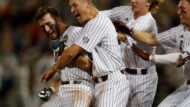 Jun 16, 2018; Omaha, NE, USA; Mississippi  State Bulldogs shortstop Luke Alexander (7) is mobbed by his teammates after hitting a walkoff single to defeat the Washington Huskies in the ninth inning during the College World Series at TD Ameritrade Park. Mandatory Credit: Bruce Thorson-USA TODAY Sports
