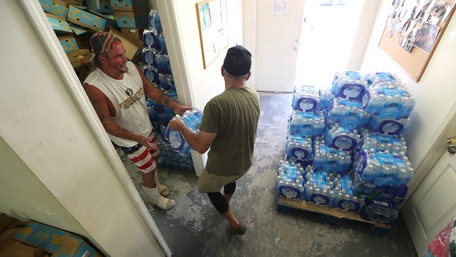 Ronald Custer, left and Frank Rohrer work to bring water into the First Baptist Church East Point as they prepare to hand out emergency supplies to residents after a wildfire ripped through the area consuming more than 30 homes.
