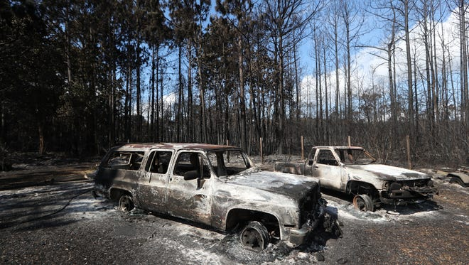Vehicles that have been burned out are left destroyed on the Thornburg property Tuesday in Eastpoint, Fla. where a wildfire, still smoldering, ripped through the area consuming more than 30 homes.