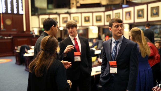 Aiden Dunaway of Taylor County, right, joins fellow students from around the state of Florida on the floor of the House as they debate at the Capitol Wednesday during their Florida 4-H Citizenship program. The program, which introduces students to the inter-workings of state legislation, began in 1973.