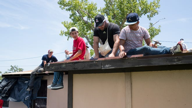 Joshua Hauser, Angelo Sanchez and Jacob Peeler volunteering with the Bounce recovery project helps replace the a roof damaged by Hurricane Harvey on a home in Rockport on Wednesday, July 18, 2018.
