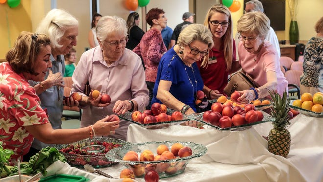 Atria Hacienda, a senior living home, residents grab some fruit after a cook-off on Thursday, July 19, 2018 in Palm Desert.
