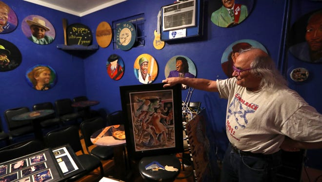 Spokesman Gary Anton arranges portraits this week in preparation for the Bradfordville Blues Club's reopening this weekend.
